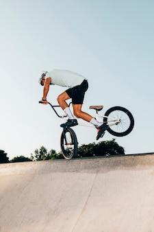 Sportlicher mann, der hoch mit fahrrad springt
