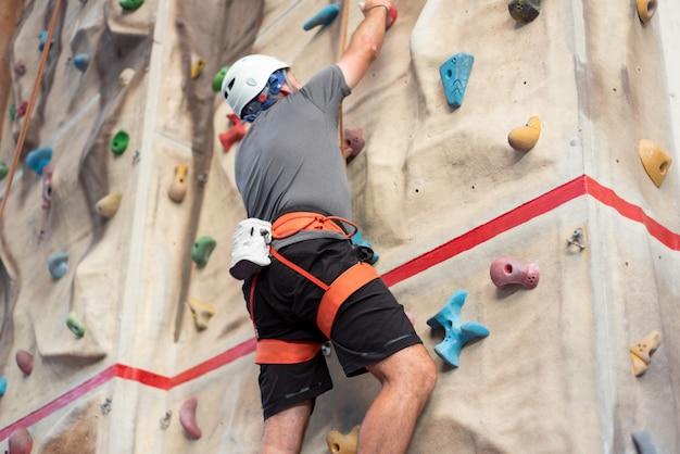 Sportlicher mann, der innenklettern in kletternder turnhalle übt.