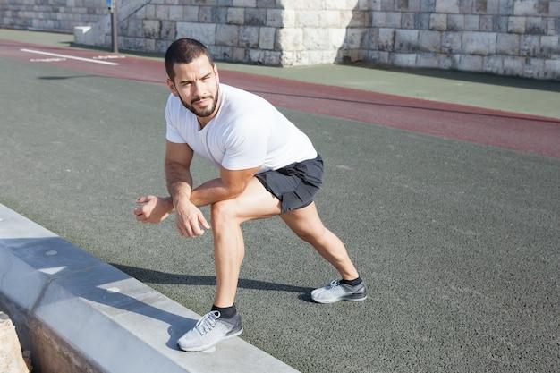 Sportlicher mann, der kalb ausdehnt und auf knie lehnt