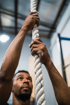 Sportlicher mann, der kletterübung tut.
