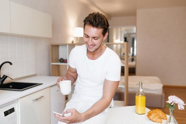 Sportlicher mann, der lächelt, während smartphonebildschirm betrachtet und tee am morgen genießt