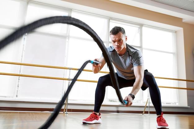 Sportlicher mann, der mit den seilen im sporthallen-sportkonzept trainiert.