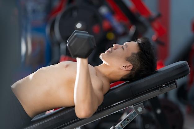 Sportlicher mann, der mit hantel im fitnessstudio trainiert