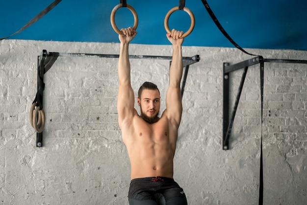Sportlicher mann der muskelaufbauübung, der intensives training im fitnessstudio auf turnringen durchführt