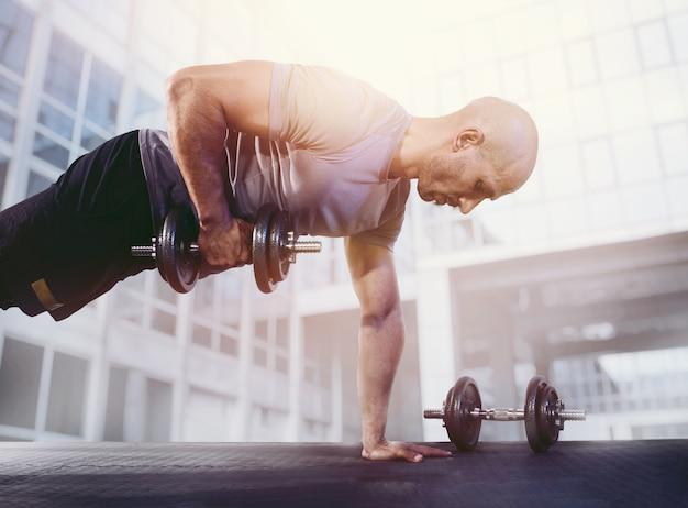 Sportlicher mann, der muskeln im fitnessstudio trainiert