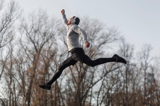 Sportlicher mann der seitenansicht, der in wald springt