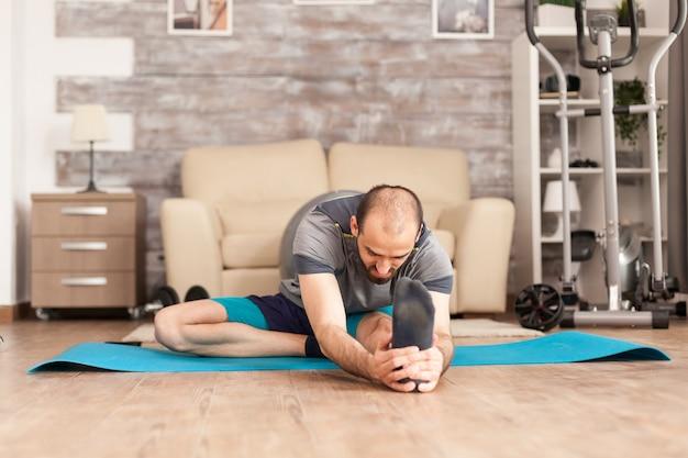 Sportlicher mann, der sich während der globalen pandemie vor dem training auf der yogamatte zu hause ausstreckt.