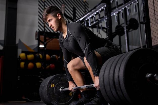 Sportlicher mann, der training und bodybuilding mit hantelgewicht im dunklen fitnessstudio und im fitnessclub hat. junger kaukasischer mann im sportbekleidungstraining allein. sport-, cross-fit- und bodybuilding-konzept