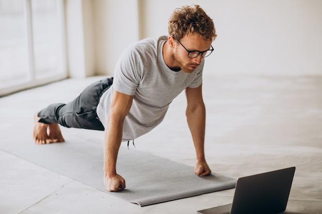 Sportlicher mann, der tutorials ansieht und yoga auf der matte praktiziert