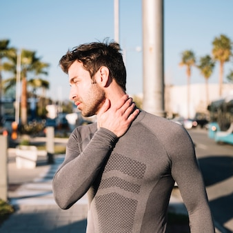 Sportlicher mann, der verletzten hals ausdehnt
