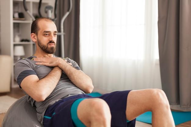 Sportlicher mann, der während der coronavirus-sperrung zu hause auf dem schweizer ball trainiert.