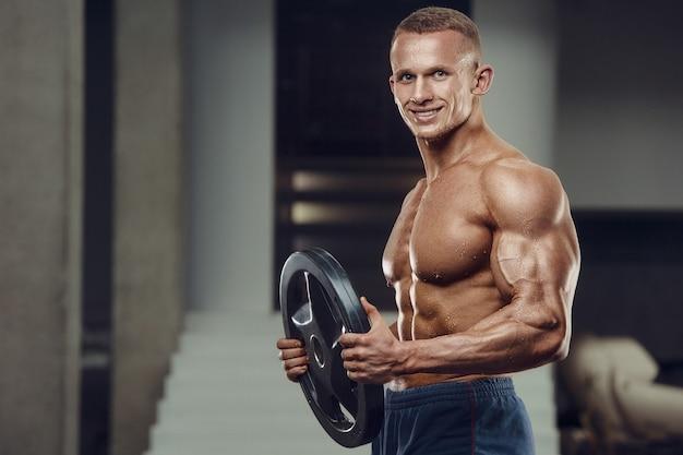 Sportlicher mann des kaukasischen krafttrainings, der bizepsmuskeln aufpumpt. starker bodybuilder mit sixpack, perfekter bauchmuskulatur, trizeps, brust, schultern im fitnessstudio. fitness- und bodybuilding-konzept
