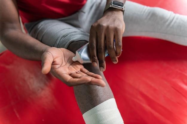 Sportlicher mann drückt heilcreme auf die handfläche, während er traumata während des trainings behandelt treating