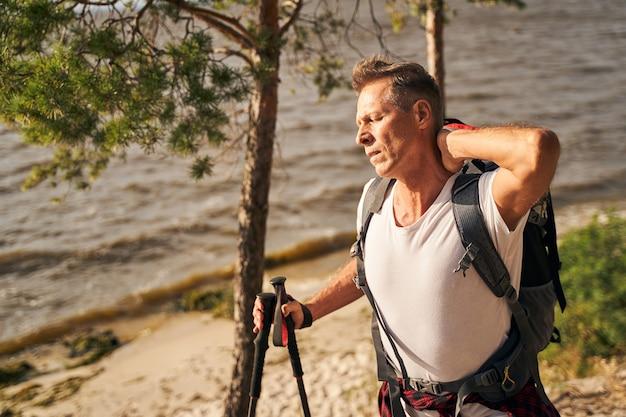 Sportlicher mann fühlt sich müde beim nordic walking mit wanderstöcken in der natur in der nähe des wellenpools