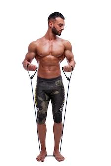 Sportlicher mann führt übungen mit einem widerstandsband durch starker mann ohne hemd mit weißem hintergrund sport