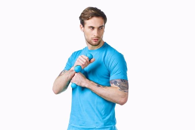 Sportlicher mann im blauen t-shirt von hanteln in den händen fitness abgeschnittene ansicht