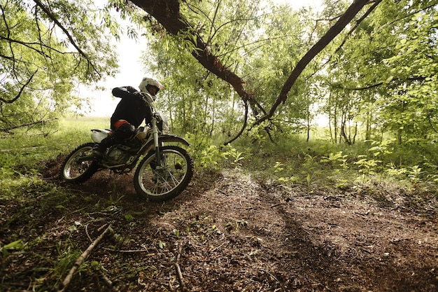 Sportlicher mann im helm, der motorrad fährt und sich wiederum beim überqueren der forststraße davon lehnt