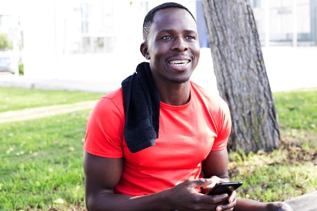 Sportlicher mann im park, der smartphone betrachtet