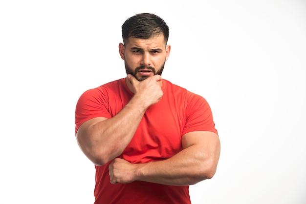 Sportlicher mann im roten hemd, der seine armmuskeln demonstriert und nachdenklich aussieht.