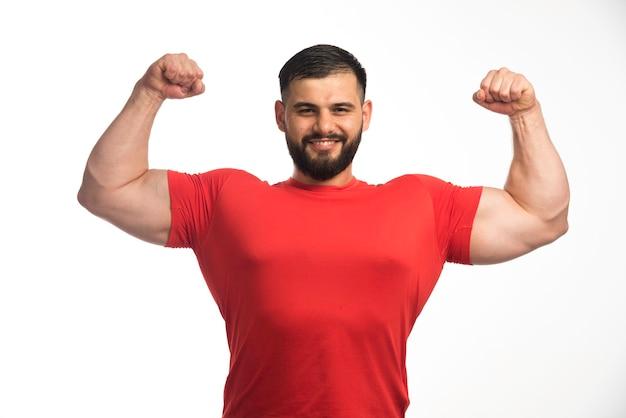 Sportlicher mann im roten hemd, der seine armmuskeln demonstriert und selbstbewusst aussieht