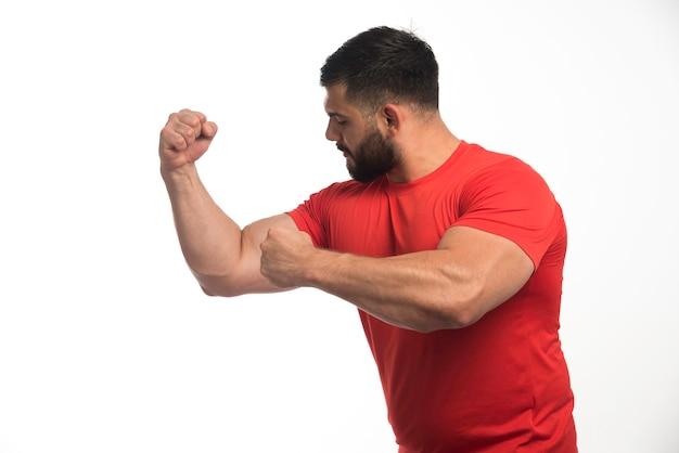 Sportlicher mann im roten hemd, der seine armmuskeln demonstriert.