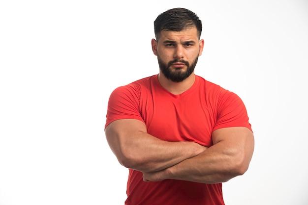 Sportlicher mann im roten hemd, der seine oberen muskeln demonstriert