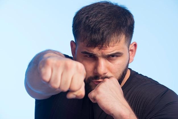 Sportlicher mann im schwarzen hemd, das boxtricks zeigt.