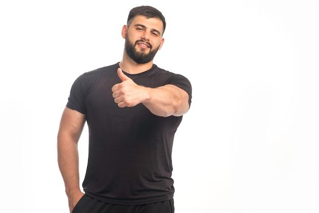 Sportlicher mann im schwarzen hemd, das daumen hoch zeichen tut