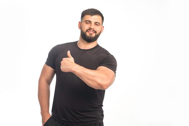 Sportlicher mann im schwarzen hemd, das daumen hoch zeichen tut.