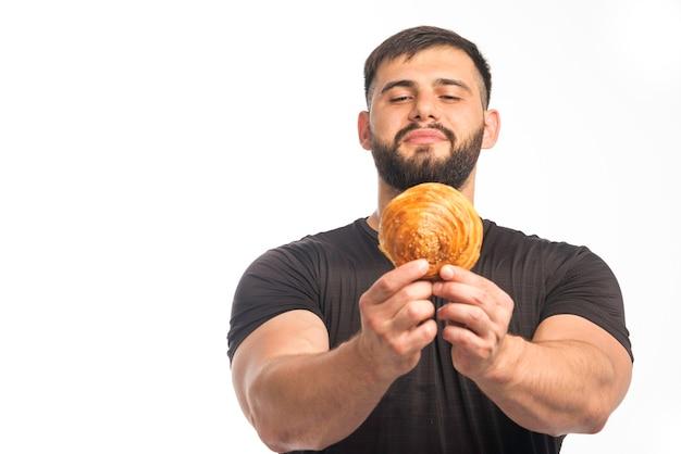 Sportlicher mann im schwarzen hemd, das donut und seine gleichgültigkeit zeigt