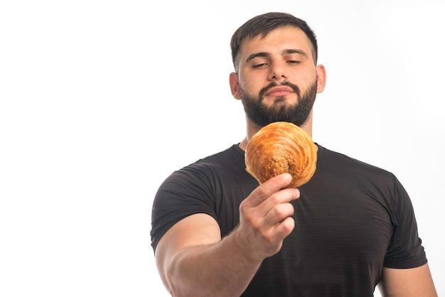 Sportlicher mann im schwarzen hemd, das donut und seine gleichgültigkeit zeigt.