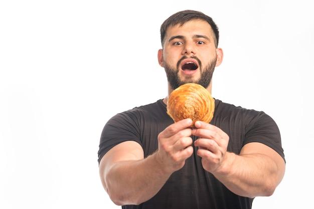 Sportlicher mann im schwarzen hemd, das donut und seinen appetit zeigt.