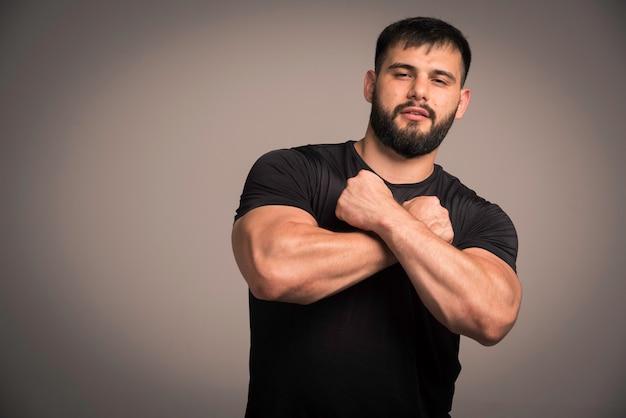 Sportlicher mann im schwarzen hemd, das fäuste in seiner brust kreuzt