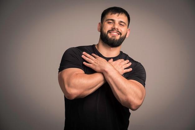 Sportlicher mann im schwarzen hemd, das hände in seiner brust kreuzt.