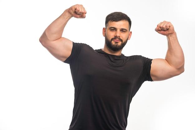 Sportlicher mann im schwarzen hemd, das seine armmuskeln zeigt.