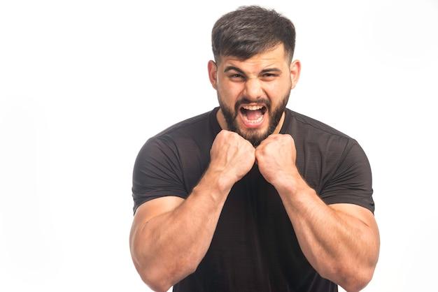 Sportlicher mann im schwarzen hemd, das seine fäuste zeigt