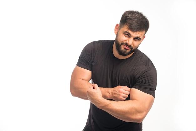 Sportlicher mann im schwarzen hemd, das seinen bizeps zeigt.
