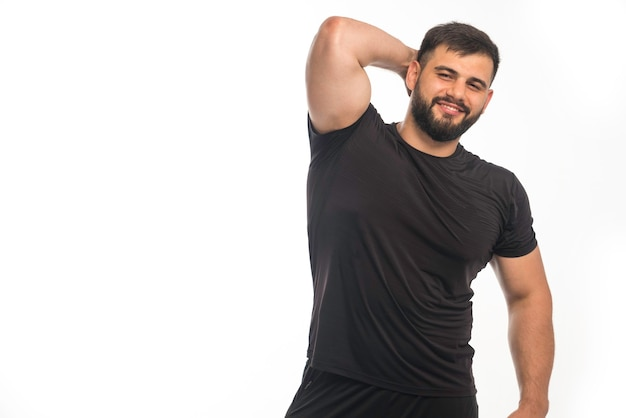 Sportlicher mann im schwarzen hemd, das seinen trizepsmuskel zeigt