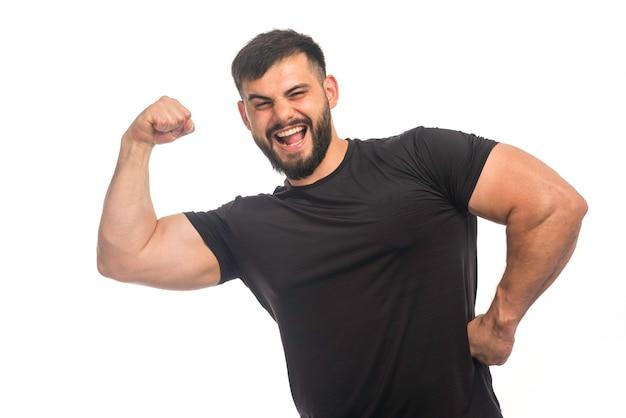 Sportlicher mann im schwarzen hemd, das stark fühlt.