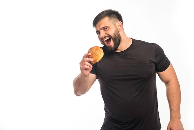 Sportlicher mann im schwarzen hemd, der einen donut hält und isst.