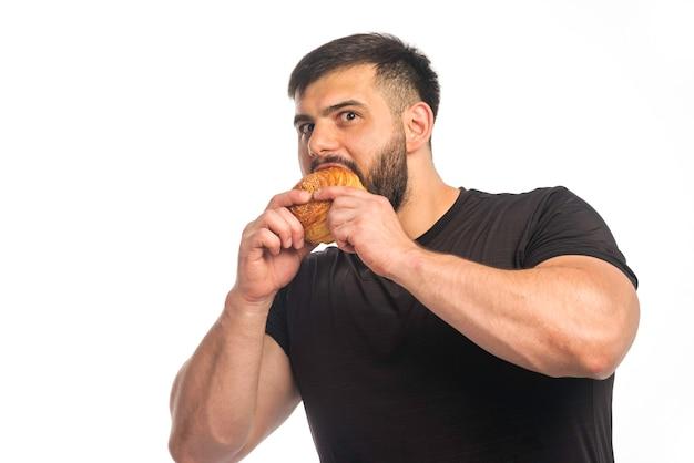 Sportlicher mann im schwarzen hemd, der einen donut isst.