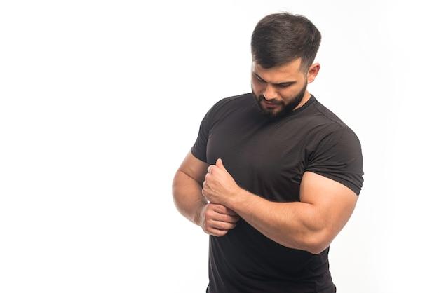 Sportlicher mann im schwarzen hemd, der seine armmuskeln demonstriert.