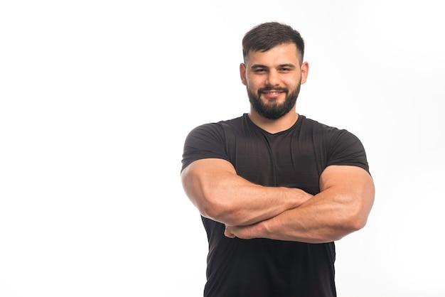 Sportlicher mann im schwarzen hemd, der seine armmuskeln schließt