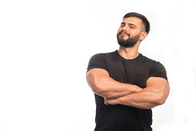 Sportlicher mann im schwarzen hemd, der seine armmuskeln schließt.