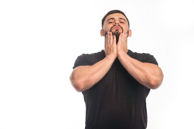 Sportlicher mann im schwarzen hemd, der seine hand auf seine wange legt