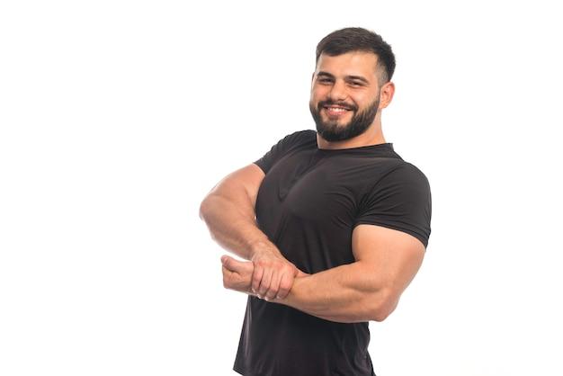 Sportlicher mann im schwarzen hemd, der seine hand zu seinen armmuskeln legt