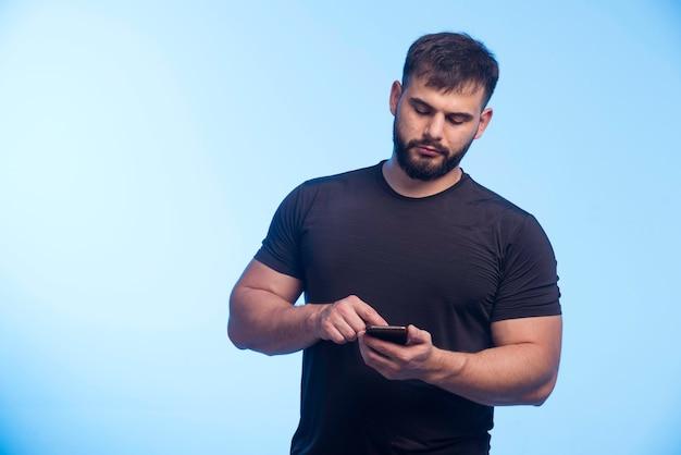 Sportlicher mann im schwarzen hemd hält das telefon und sms