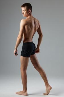 Sportlicher mann im schwarzen höschen pumpte körper auf, der lebensstil aufwirft