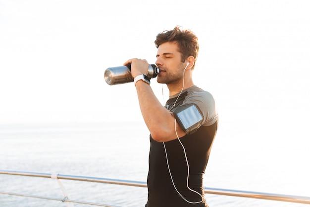Sportlicher mann im t-shirt, der musik über drahtlose kopfhörer und trinkwasser aus metallbecher hört, nach dem training am meer
