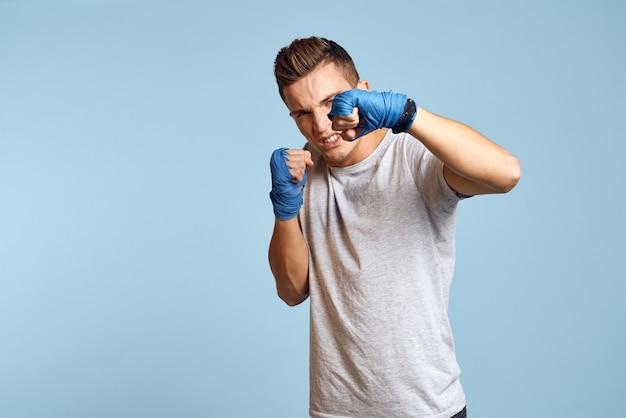 Sportlicher mann in den blauen boxhandschuhen und im t-shirt auf dem blauen hintergrund, der schlägt. beschnittene ansicht.
